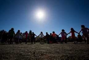 Children hold hands as students and teachers from Britannia Secondary School and Britannia Elementary School participate in a First Nations drum circle to coincide with the Youth Matters conference in Vancouver, B.C., on Tuesday, Sept. 29, 2015.