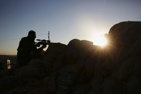 In this Nov. 12, 2015, file photo, a Kurdish peshmerga fighter stands guard in fighting against the Islamic State group as the sun rises in Sinjar, Iraq. (AP Photo/Bram Janssen, File)