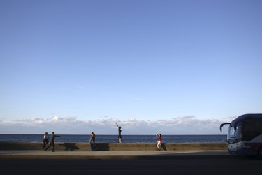 Tourists alight from the bus and pose for pictures at the seafront Malecon in Havana, January 25, 2016. REUTERS/Alexandre Meneghini