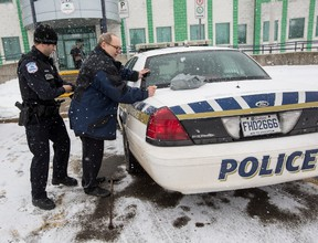Dan Smith, 65, is searched against a police cruiser by an officer at the Gatineau Police Station after refusing to pay a fine and court costs after being found guilty last summer for not having a license for a cat. Thursday January 28, 2016. Errol McGihon/Ottawa Sun/Postmedia Network