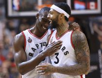 Toronto Raptors center Bismack Biyombo (8) shares a laugh with forward James Johnson (3) against the Detroit Pistons at Air Canada Centre. The Raptors beat the Pistons 111-107. Tom Szczerbowski-USA TODAY Sports