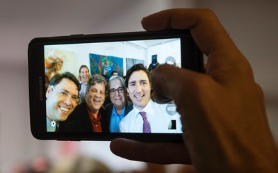 Liberal Leader Justin Trudeau takes a photo with supporters during a campaign stop at a coffee shop,  Monday, October 5, 2015 in Oakville, Ont. THE CANADIAN PRESS/Paul Chiasson