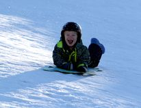 Solomon Waye laughs as he speeds down Thrill Hill while sledding with his family on Friday January 29, 2016 in Grande Prairie, Alta. With no school on Friday, families made their way to the hill which had gotten slippery after the rain earlier in the week, making sledders gain a lot of speed and distance heading down the hill. Jocelyn Turner/Grande Prairie Daily Herald-Tribune/Postmedia Network
