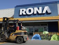 A man drives a forklift in front of a Rona home improvement store in St. Eustache, Que., just outside Montreal, on July 16, 2015. The Lowe's home improvement chain is buying Quebec-based Rona Inc. in a deal valued at $3.2 billion. (THE CANADIAN PRESS/Ryan Remiorz)