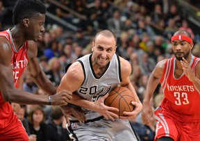San Antonio Spurs guard Manu Ginobili (20), of Argentina, drives around Houston Rockets center Clint Capela, left, of Switzerland, as Houston's Corey Brewer looks on during the second half of an NBA basketball game, Saturday, Jan. 2, 2016, in San Antonio. San Antonio won 121-103. (AP Photo/Darren Abate)