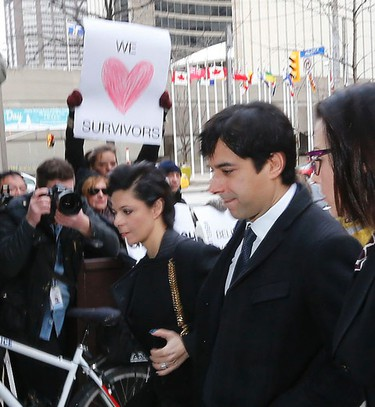 Facing some signs from protesters, Jian Ghomeshi arrives with lawyer Marie Henein (l) for the continuation of his trial at Old City Hall court in Toronto on Thursday February 4, 2016. (Michael Peake/Toronto Sun)