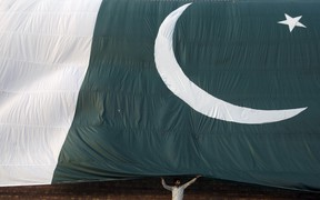 A man adjusts a Pakistani flag on a building. FILE pic. (REUTERS/Mohsin Raza)