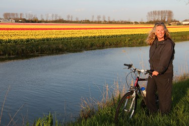 Janie Robinson pauses with her bike along one of the placid canals that line Hollands fabulous flower fields. BRIAN QUINN PHOTO