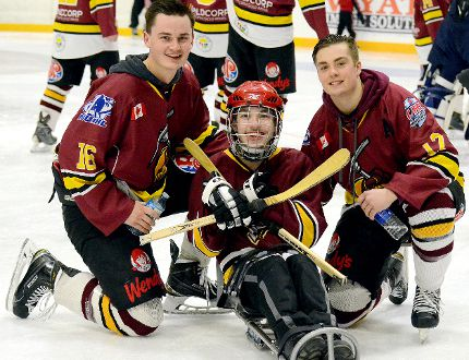 Nick Gelinas, a sledge-hockey enthusiast, was one of the many fans who took advantage of the Skate With The Rock session that followed Sunday afternoon's NOJHL game at the McIntyre Arena. Rock defenceman Joe Olson, left, and forward Jordan Rendle — who scored the game-winning goal in overtime — were two of the players happy to see Gelinas and so many others shared some time with them on Super Bowl Sunday. THOMAS PERRY/THE DAILY PRESS