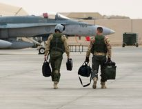 Two Canadian CF-18 Hornet pilots walk towards a fighter jet at Camp Patrice Vincent after returning from a mission during Operation IMPACT on January 18, 2015. DND/Combat Camera
