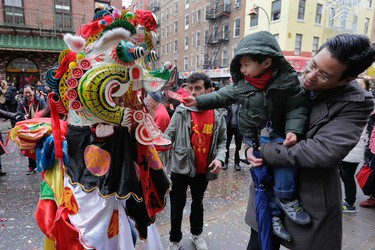 A lion dancer from the Tai Pun Residents Association accepts an offering in a red envelope during a Lunar New Year celebration, in New York's Chinatown neighborhood, Monday, Feb. 8, 2016. Monday marks the first day of the Year of the Monkey � the ninth animal on the Chinese zodiac calendar. The weeklong holiday, known as the Spring Festival in China, is focused on family reunion and is a time when students and migrant workers return to their hometowns.(AP Photo/Richard Drew)