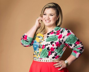 """In this March 4, 2015 file photo, American singer and songwriter Kelly Clarkson poses for a portrait to promote her album """"Piece by Piece"""" in New York. Clarkson has written a new song and a bedtime story for kids. """"River Rose and the Magical Lullaby,"""" will be released in October by HarperCollins Children's Books. (Photo by Victoria Will/Invision/AP, File)"""