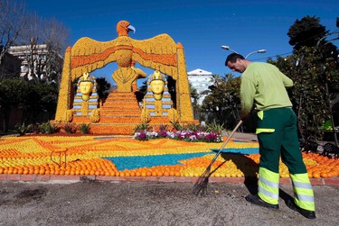 """A worker puts the final touch to a replica of a giant eagle and pharaons made with lemons and oranges which shows a scene of the movie """"Cleopatra"""" during the Lemon festival in Menton, France, February 10, 2016. Some 140 metric tons of lemons and oranges are used to make displays during the 83rd festival, which is themed """"Cinecitta"""", and runs from February 13 through March 2.   REUTERS/Eric Gaillard"""