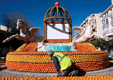 """A worker puts the final touch to a replica of fountain made with lemons and oranges which shows a scene of the movie """"La Dolce Vita"""" during the Lemon festival in Menton, France, February 10, 2016. Some 140 metric tons of lemons and oranges are used to make displays during the 83rd festival, which is themed """"Cinecitta"""", and runs from February 13 through March 2.   REUTERS/Eric Gaillard"""