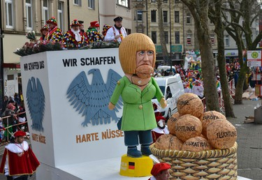 A carnival float depicting Angela Merkel cracking tough nuts called Refugees, Europe and Migration during the traditional carnival parade in Cologne, western Germany, Monday, Feb. 8, 2016. Many carnival parades in Germany were canceled because of heavy stormy weather. The foolish street spectacle in Cologne, normally watched by hundreds of thousands of people, is the highlight in Germany's carnival season on Rose Monday. (AP Photo/Martin Meissner)