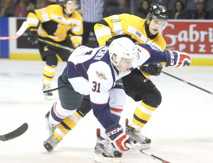Kingston Frontenacs' Warren Foegele ties up Windsor Spitfires' Mikhail Sergachev during the first period of Ontario Hockey League action on Friday at the Rogers K-Rock Centre on Friday night. (Elliot Ferguson/The Whig-Standard)