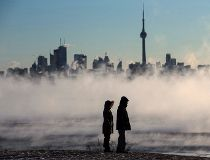 Steam rises as people look out on Lake Ontario in front of the skyline during extreme cold weather in Toronto on Saturday