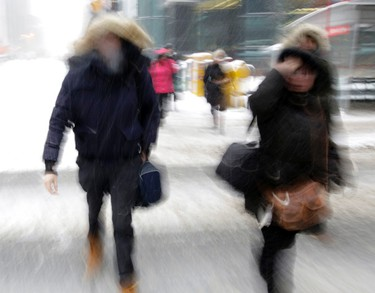 People commute through downtown Ottawa during a winter storm, February 16, 2016. (Darren Brown/Postmedia Network)