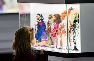 A young visitor admires Barbie dolls at Barbie Expo, a permanent exhibit that celebrates the best-selling doll's nearly six decades as a fashionista, Friday, February 12, 2016 in Montreal. THE CANADIAN PRESS/Paul Chiasson