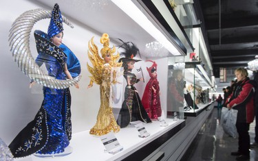 Visitors admire Barbie dolls at Barbie Expo, a permanent exhibit that celebrates the best-selling doll's nearly six decades as a fashionista, Friday, February 12, 2016 in Montreal. THE CANADIAN PRESS/Paul Chiasson
