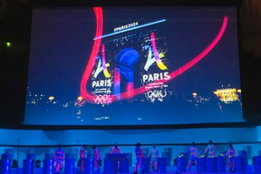 Dancers perform on stage as the Eiffel Tower-shaped bid logo for the Paris 2024 is projected on the Arc de Triomphe on a giant screen during the presentation of Paris as candidate to host the 2024 Olympic Games Wednesday, Feb. 17, 2016. (AP Photo/Francois Mori)