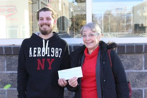 Justin Carriere, left, and Linda Jacejko, right, accept a cheque from Eastalta Co-op as part of its employee community involvement program. Carriere contributed at least 100 volunteer hours to the Habitat for Humanity build in Vermilion.