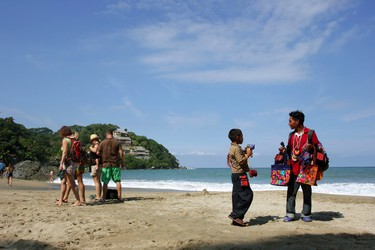 In this Dec. 2, 2015 photo, a vendor, right, walks away from a  group of tourists at Playa de los Muertos, or Beach of the Dead, in Sayulita, Mexico. The once tranquil fishing town of Sayulita has matured to a top travel and retirement destination in Mexico. (AP Photo/Manuel Valdes)