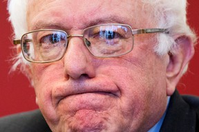 Listening journalists and television cameras are reflected in the glasses of Democratic presidential candidate, Sen. Bernie Sanders, I-Vt. as he meets with leaders of nine historic civil rights groups, at the National Urban League Washington Bureau in Washington on Thursday Feb. 18, 2016. (AP Photo/Jacquelyn Martin)