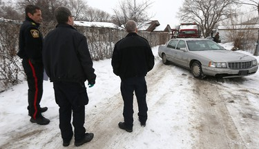 Police look on as an older-model Cadillac Deville is towed from the backyard of a duplex at 15 Treger Bay in the Valley Gardens area of Winnipeg on Fri., Feb. 19, 2016. It's believed a search warrant was executed at the location in relation to the disappearance of 17-year-old Cooper Nemeth. Kevin King/Winnipeg Sun/Postmedia Network