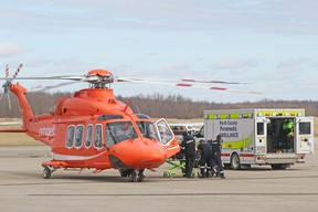 Perth County paramedics transfer a patient to an Ornge air ambulance at the Stratford airport Monday morning after two people were seriously injured in an apparent carbon monoxide leak at a business in Mitchell. The patient was airlifted to Hamilton to receive treatment in a hyperbaric chamber, which helps remove carbon monoxide from the blood. Mike Beitz/Stratford Beacon Herald/Postmedia Network