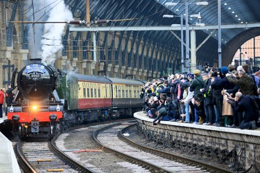 """People watch from a railway platform as the Flying Scotsman steam engine prepares to leave Kings Cross station in London, February 25, 2016. Celebrity locomotive 60103 Flying Scotsman made its official return to steam with a celebratory """"Inaugural Run"""" along the East Coast Mainline after a decade-long 4.2 million British Pounds ($5.8 million) restoration.  REUTERS/Paul Hackett      TPX IMAGES OF THE DAY"""