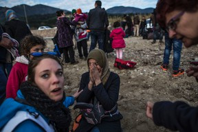 A Syrian woman reacts after her arrival with other refugees and migrants from the Turkish coast to Mytilene on the Greek island of Lesbos, Tuesday, Feb. 23, 2016.  Nearly 100,000 migrants and refugees have traveled to Greek islands from nearby Turkey so far this year. (AP Photo/Manu Brabo)