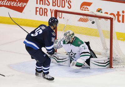 Feb 23, 2016; Winnipeg, Manitoba, CAN;  Winnipeg Jets left wing Andrew Ladd (16) shoots the puck past Dallas Stars goalie Antti Niemi (31) during the second period at MTS Centre. Mandatory Credit: Bruce Fedyck-USA TODAY Sports
