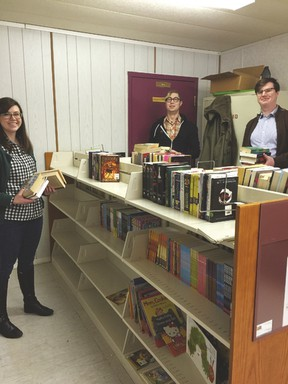Books are added to the mini-library at Paul Band. - Photo by Marcia Love