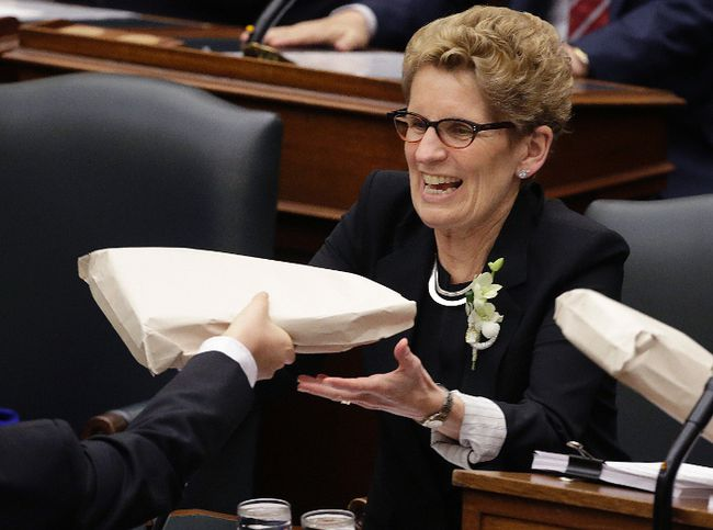 Premier Kathleen Wynne gets handed the 2016 Budget  in Toronto, Ont. on Thursday February 25, 2016. (Postmedia Network)