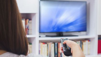 Woman turning on TV