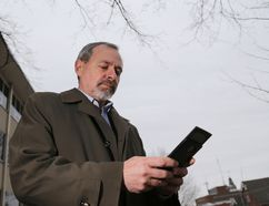 Luke Hendry/The Intelligencer Hastings County chief administrative officer Jim Pine uses his mobile phone outside county headquarters in Belleville Tuesday. City residents enjoy widespread mobile phone service, but there are large gaps in rural coverage. Pine is a leader of a proposal to close those gaps.
