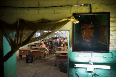 """In this March 1, 2016 photo, a picture of revolutionary hero Ernesto """"Che"""" Guevara decorates a the wall inside a state-run warehouse where workers select tobacco leaves in the province of Pinar del Rio, Cuba. Tobacco operations receive tourists on group visits organized by state tourism agencies and foreigners by the hundreds receive lectures on Cuban tobacco. (AP Photo/Ramon Espinosa)"""