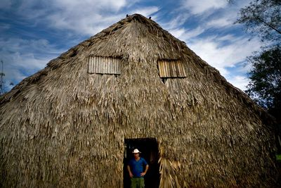 In this Feb. 27, 2016 photo, Yoberlan Castillo Garcia, 30, poses for a portrait in the doorway of the barn where tobacco leaves are dried on his family's farm in Vinales in the province of Pinar del Rio, Cuba. The barn, made of dried palm leaves and wood, is also where they park a motorcycle and horse riding equipment. (AP Photo/Ramon Espinosa)