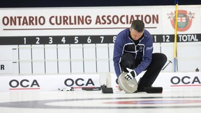 Skip Wayne Middaugh wipes ice from the bottom of a rock before throwing during his match against Team Kean at the Ontario Curling Championships at the Flight Exec Centre in Dorchester, Ont., on Feb. 5, 2015. (CRAIG GLOVER/The London Free Press)