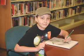 Duncan Mackay shades in a comic book hero in his sketchbook at the Stony Plain Public Library. The young artist is lending his skills to the library in creating a comic book that will be used to teach about misinformation found online. - Photo by Marcia Love