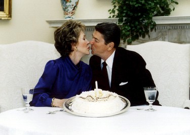U.S. President Ronald Reagan and his wife Nancy kiss on their wedding anniversary in the White House in this March 4, 1985 file photo. REUTERS/Files