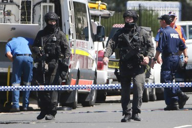 Police Tactical Group officers walk on a cordoned off street of an industrial section of Ingleburn, in suburban Sydney, Monday, March 7, 2016 as police respond to a shooting. (AP Photo/Rick Rycroft)