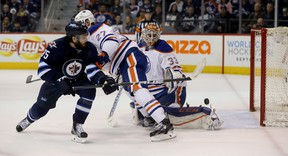 Winnipeg Jets' Mathieu Perreault (85) battles with Edmonton Oilers' Adam Clendening (27) in front of Oilers' goalie Cam Talbot (33) during second period NHL hockey action, in Winnipeg on Sunday, Mar. 6, 2016.