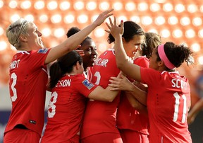 Canada's Christine Sinclair, centre, is congratulated after scoring a goal against Trinidad & Tobago during second-half CONCACAF Olympic qualifying tournament action in Houston on Feb. 14, 2016. (AP Photo/David J. Phillip)