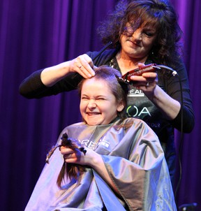 Sudbury Secondary School student Cassidy Barrett holds what's left of her long hair while getting her head shaved during a school fundraiser at Sudbury Secondary on Thursday. Two teachers and six students had their hair cut or shaved to be donated and to show support for Vicki Ashick, a teacher recently diagnosed with breast cancer. Ben Leeson/The Sudbury Star/Postmedia Network