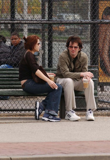 2004: Neve Campbell takes a break for a cigarette with her boyfriend in New York City. (WENN.COM)