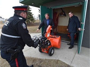 EPS officers Const. Uwe Steil (centre) and acting Sgt. Ron Smithman (L) return close to $12,000 in recovered snow cleaning equipment stolen from the North Millbourne Community League hall as league vice-president Brandon Kowalczyk (R) watches in Edmonton, March 15, 2016. (ED KAISER/PHOTOGRAPHER)