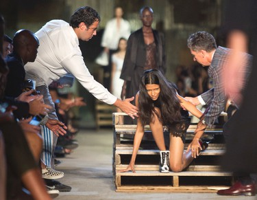 A model falls and gets help back to her feet during the fashion show for the Givenchy Spring 2016 collection at Fashion Week on, Friday, Sept. 11, 2015, in New York. (AP Photo/Bebeto Matthews)