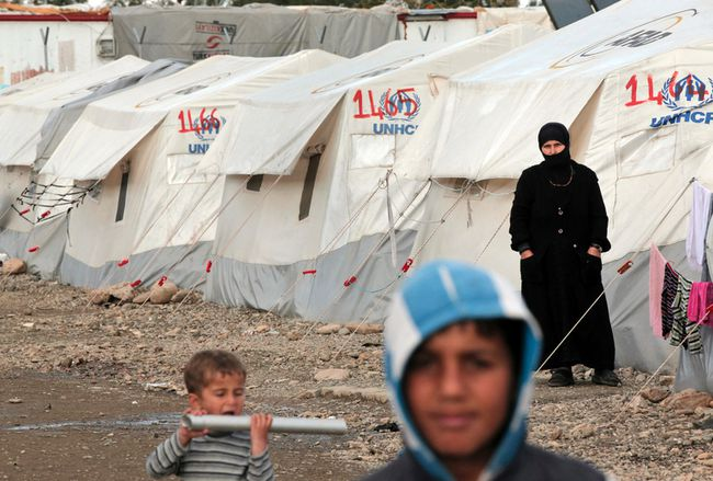 A Syrian refugee stands outside the family tent at a refugee camp for Syrian refugees in Islahiye, Gaziantep province, southeastern Turkey,Wednesday, March 16, 2016. (AP Photo/Lefteris Pitarakis)